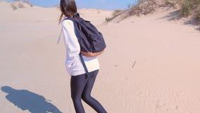 O viajante da menina anda na estação baixa vazia da praia da areia do mar nas dunas em férias filme
