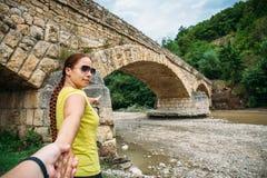 O viajante da moça conduz o homem à mão à ponte antiga foto de stock royalty free