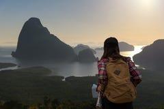 O viajante das mulheres com trouxa verifica o mapa para encontrar sentidos Foto de Stock Royalty Free
