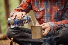 O viajante do homem derrama a água de uma garrafa em uma caneca do metal fotografia de stock royalty free