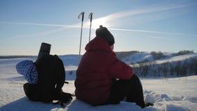 O viajante do homem senta o descanso em um penhasco nas montanhas do inverno e no chá das bebidas de uma garrafa térmica Opinião  filme