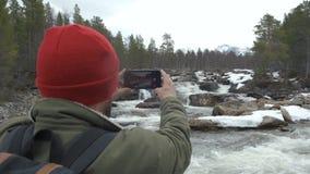 O viajante em um chapéu vermelho com uma parte traseira completa da trouxa parou para tomar uma foto de um rio da montanha Concei video estoque