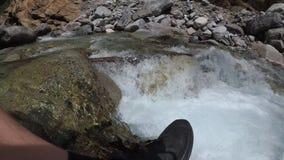 O viajante explora um rio da montanha na câmera da ação vídeos de arquivo