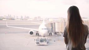 O viajante fêmea bonito anda acima à janela terminal da sala de estar do aeroporto para estar e apreciar a ideia de passar aviões vídeos de arquivo