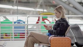 O viajante fêmea está descansando na sala de espera da estação, está sentando e está usando o telefone filme
