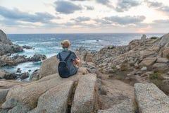 O viajante fêmea novo de solo olha um por do sol bonito em rochas espetaculares do Testa do Capo, Sardinia, Itália fotos de stock royalty free