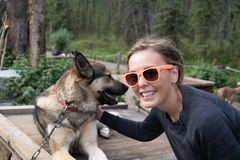 O viajante fêmea pets um cão de trenó ronco do Alasca no parque nacional de Denali fotografia de stock royalty free