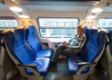 O viajante masculino senta-se perto de uma janela no carro Fotos de Stock