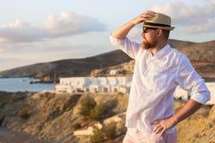 o viajante masculino Vermelho-farpado em uma camisa branca está nos raios do sol da manhã em um banco íngreme perto do mar imagens de stock