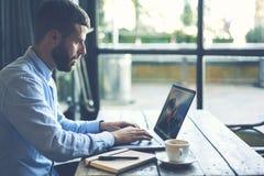 O viajante novo do blogger do moderno em um revestimento da sarja de Nimes que datilografa no teclado do laptop conectou ao Inter fotografia de stock