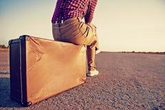 O viajante senta-se na mala de viagem Fotos de Stock