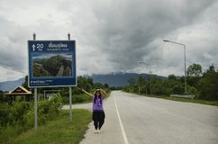 O viajante tailandês das mulheres que levanta para toma a foto com o polo do guia do sinal da distância Fotos de Stock Royalty Free
