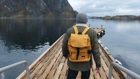 O viajante vai ao cais Vestido em um revestimento e um chapéu feito malha e uma trouxa amarela Vista traseira Noruega Lofoten video estoque