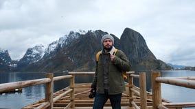 O viajante vai em um cais de madeira vestido em um revestimento e um chapéu feito malha e uma trouxa amarela Vista traseira Norue video estoque