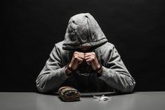 O viciado em drogas foi prendido para o uso da droga na tabela sofrimento do apego em um fundo preto escuro foto de stock royalty free