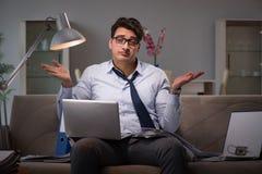 O viciado em trabalho do homem de negócios que trabalha tarde em casa imagens de stock royalty free