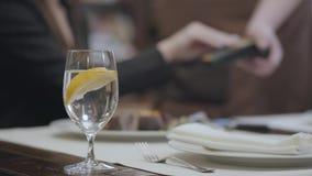 O vidro com água e o limão no restaurante da tabela e no fundo é uma conta da verificação do pagamento da mulher filme
