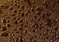 O vidro com água natural deixa cair a textura de bronze do ouro Imagens de Stock Royalty Free