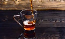 O vidro com o chá que derrama com líquido com espirra e deixa cair da água O copo que derrama com água ou chá com espirra na obsc imagens de stock royalty free