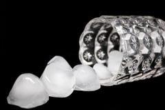 O vidro com os filhotes do gelo nele e em torno dele em preto - imagem fotografia de stock royalty free