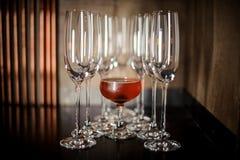 O vidro de cocktail elegante encheu-se com o cocktail alcoólico vermelho saboroso entre vidros do champanhe fotografia de stock royalty free