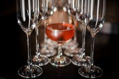O vidro de cocktail elegante encheu-se com o cocktail alcoólico vermelho saboroso entre vidros vazios do champanhe fotos de stock