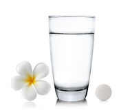 O vidro de comprimidos da água e o frangipani florescem no backgr branco Fotos de Stock Royalty Free