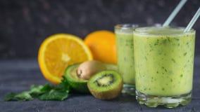 O vidro de dois vidros encheu-se com o batido do abacate em uma tabela de madeira preta com frutos Alimento do vegetariano da die Fotografia de Stock