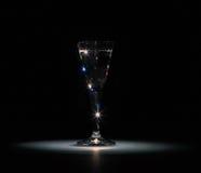 O vidro de tiro da vodca custa na obscuridade em um ponto claro em um fundo preto Imagens de Stock Royalty Free