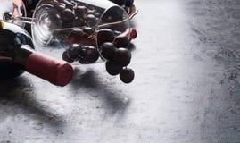 O vidro de vinho com uva vermelha aglomera-se, garrafa do vinho no fundo escuro lugar para seu projeto foto de stock royalty free