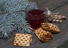 O vidro do chá decorado com cookies diferentes e um ramo de um abeto Imagens de Stock Royalty Free