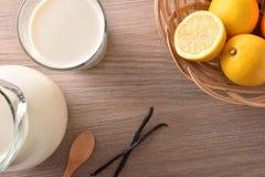 O vidro do leite em limões de madeira da tabela e a canela cobrem Foto de Stock