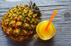 O vidro do suco de abacaxi fresco e o abacaxi maduro frutificam na tabela de madeira rústica Suco de abacaxi recentemente espremi Fotografia de Stock