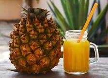 O vidro do suco de abacaxi fresco e o abacaxi maduro frutificam na tabela de madeira rústica Suco de abacaxi recentemente espremi Imagens de Stock