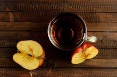 O vidro do vinagre de sidra de maçã e duas metades de uma maçã Foto de Stock Royalty Free