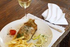 O vidro do vinho branco com pescadas fritadas pesca e microplaquetas foto de stock