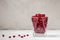 O vidro encheu-se com as sementes da romã na tabela Imagem de Stock