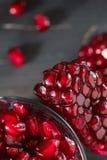 O vidro encheu-se com as sementes da romã na tabela Fotografia de Stock Royalty Free