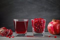 O vidro encheu-se com as sementes da romã na tabela Imagens de Stock