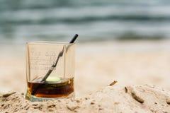 O vidro encheu-se com o uísque irlandês na praia da areia Fotos de Stock