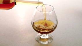 O vidro limpo fulled com aguardente de alta qualidade do ouro no restaurante vídeos de arquivo