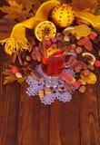 O vinho, as porcas e os doces ferventados com especiarias no fundo amarelam as folhas de bordo Fotografia de Stock Royalty Free