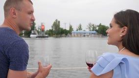 O vinho bebendo dos pares da família no iate, pares felizes bebe a bebida vermelha no mar, dois povos em férias vídeos de arquivo