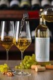 O vinho branco é derramado em um vidro no fundo de outras garrafas de uvas para vinho e de porcas imagens de stock