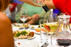 O vinho branco é derramado em uma garrafa em uma tabela festiva fotos de stock