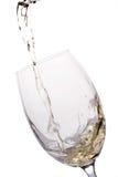 O vinho branco derramou em um vidro imagem de stock