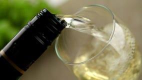O vinho branco derramou no vidro na tabela com uvas filme
