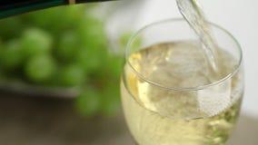 O vinho branco derramou no vidro na tabela com uvas video estoque