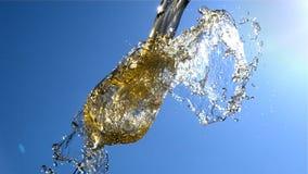 O vinho branco está derramando dentro a um vidro com céu azul e luz do sol no fundo no movimento lento video estoque