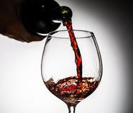 O vinho da uva derramou da garrafa no vidro de vinho do vidro Fotografia de Stock